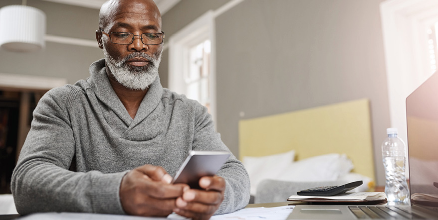Image of older man looking at his cell phone.